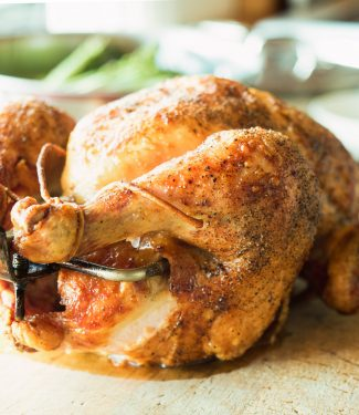 Rotisserie chicken cooked over fire. Spit-roasting self bastes the bird. The result - a succulent, crispy bird served up with a simple board sauce.