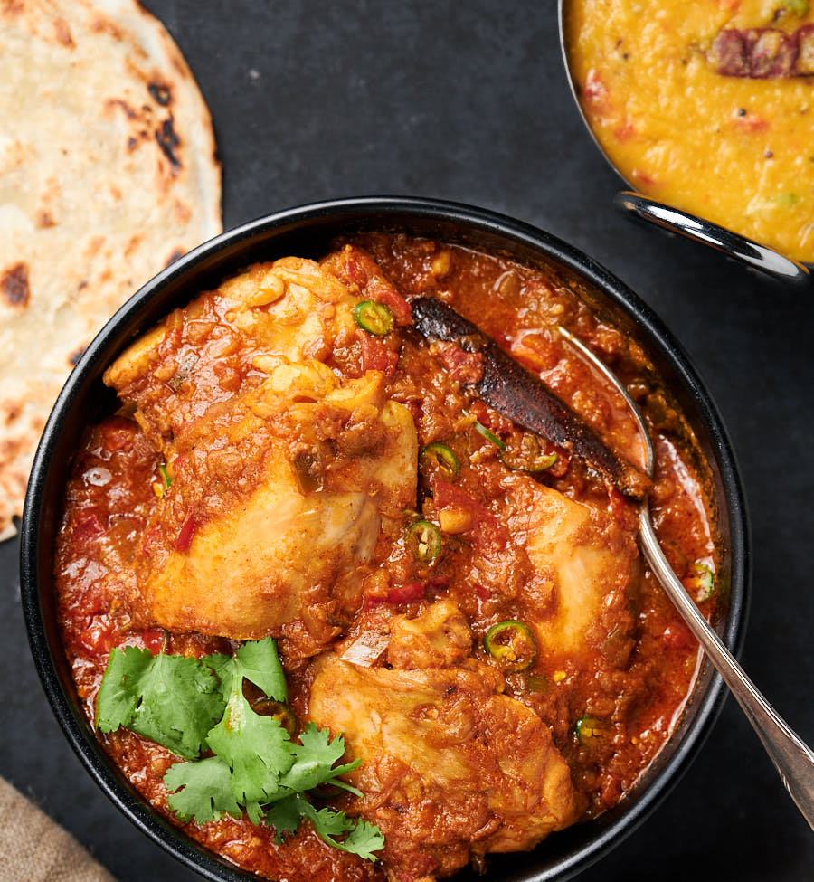 Simple chicken curry in a bowl with serving spoon from above.