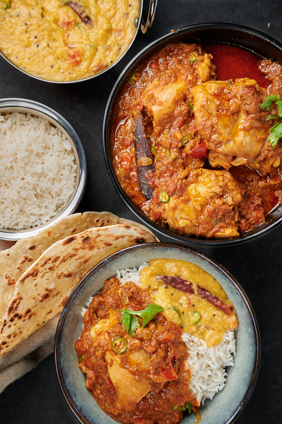 Simple chicken curry in a serving bowl with rice, paratha, and dal from above.