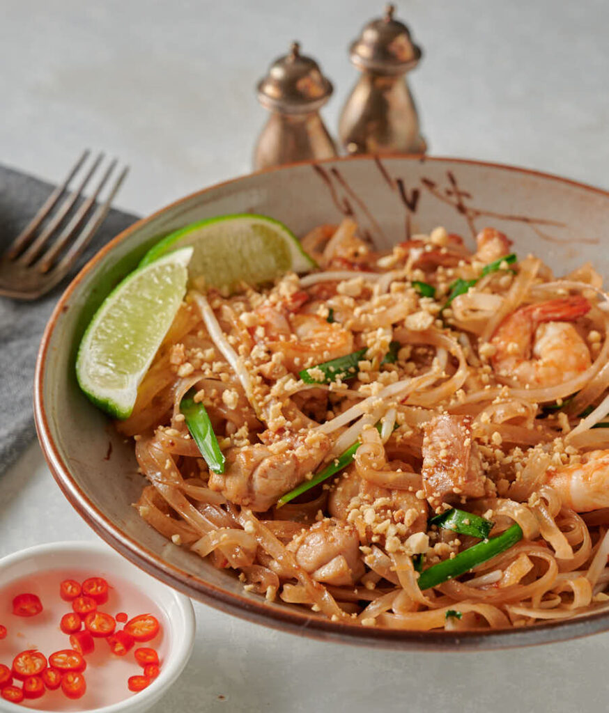 Easy pad Thai garnished with lime in a bowl. From the front.