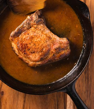 To make perfect pan fried pork chops, pick your chops wisely, use a heavy pan and finish the chop in the oven.