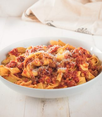 Neapolitan ragu on pappardelle in a white bowl.