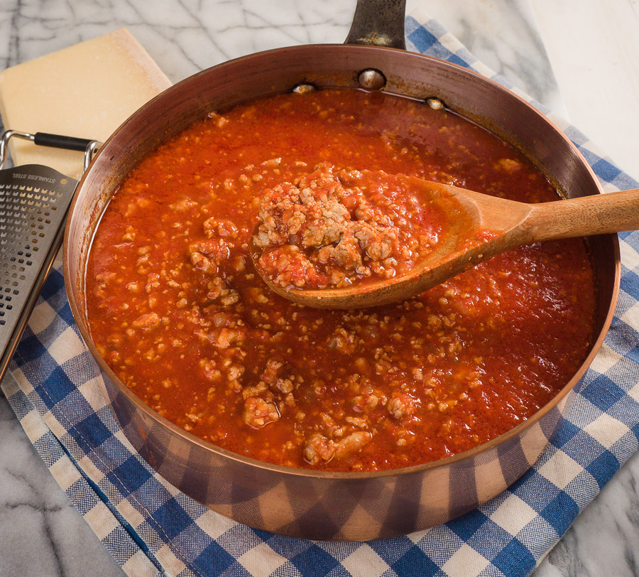 Neapolitan ragu in a pot with a ladle.