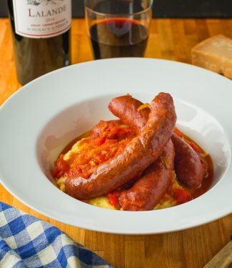 Upscale sausage with peppers served with parmesan polenta.