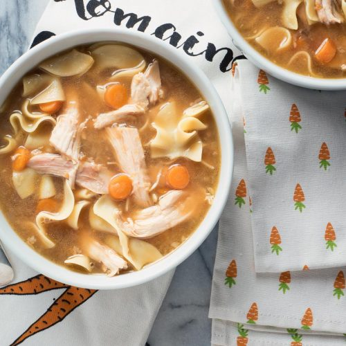 Turkey noodle soup with carrots in a white bowl.