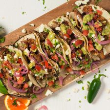 Loaded carnitas tacos with queso, pico, pickled onions and avocado tomatillo salsa.
