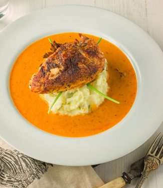 Chicken with creole cream sauce on a bed of green chili, garlic mashed potatoes.