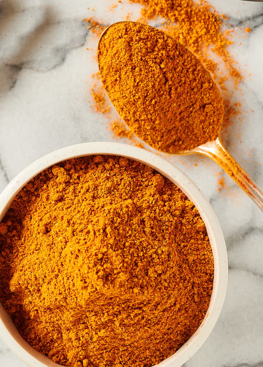 Indian restaurant spice mix in a bowl with a spoonful of spice from the top.