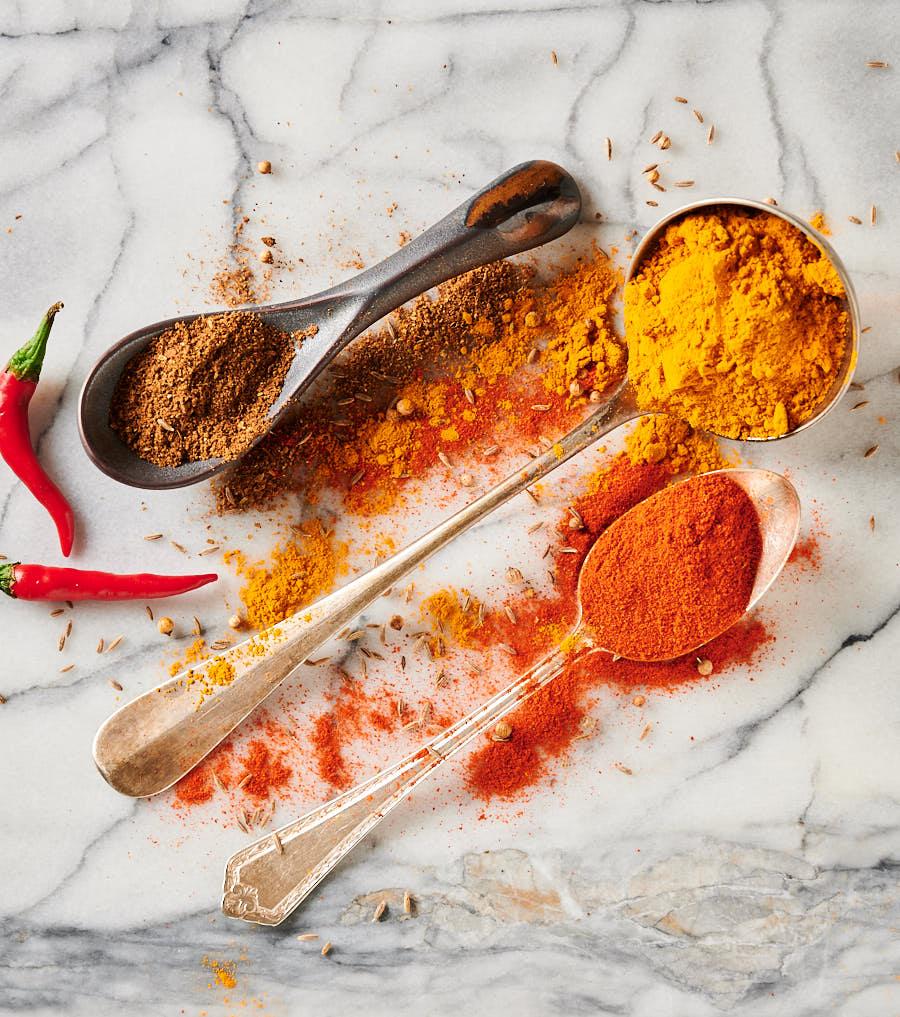 Spoons filled with turmeric, garam masala and Kashmiri chili powder.
