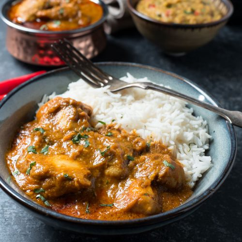 Bowl of chicken madras with rice from the front.