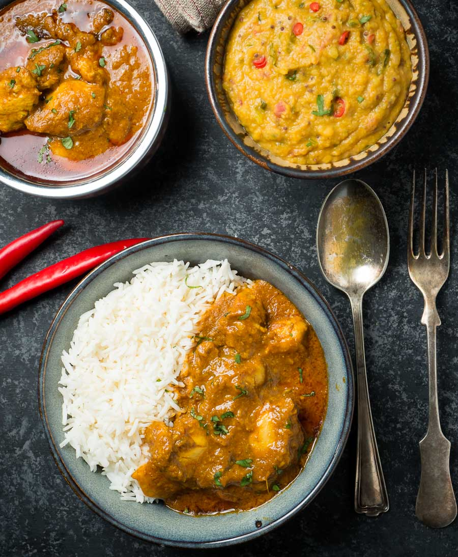 Bowl of chicken madras curry with rice and lentils from above.