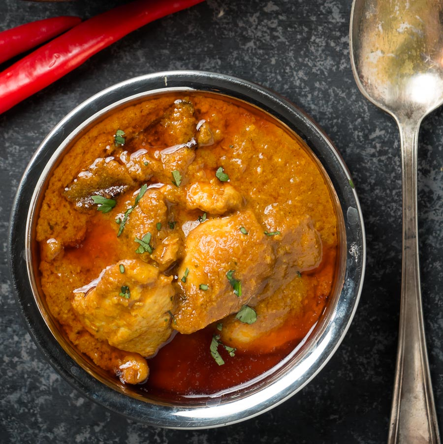 Chicken madras in an Indian copper bowl from above.