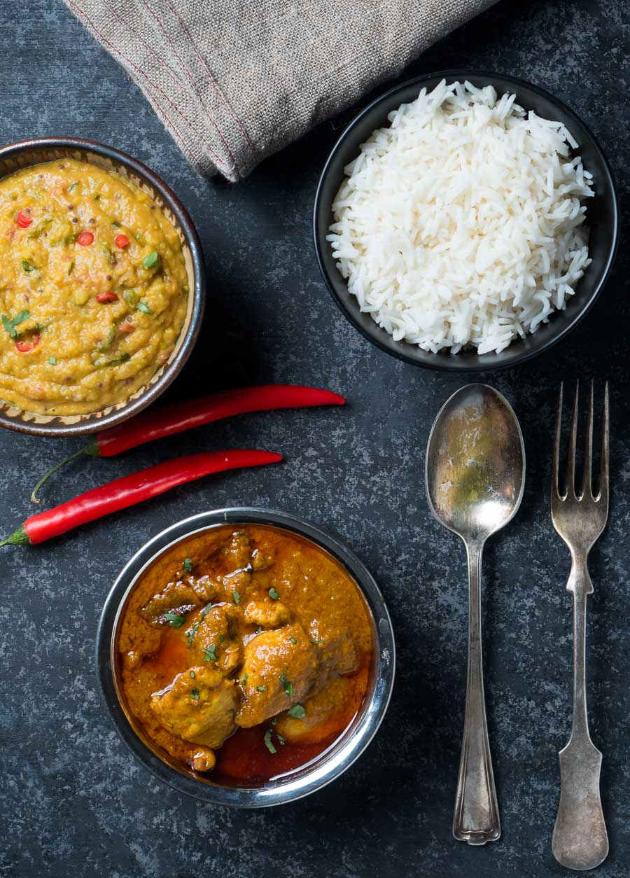 Chicken madras, masoor dal and rice serving bowls from above.