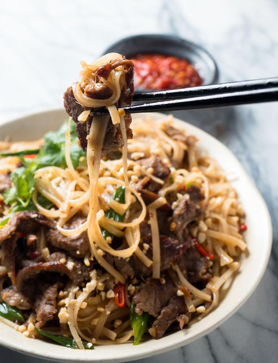 Thai beef noodles - bite held in chopsticks.