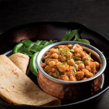 Chana masala in a copper bowl from the front.