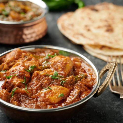 Dopiaza curry in an Indian copper bowl with parathas.