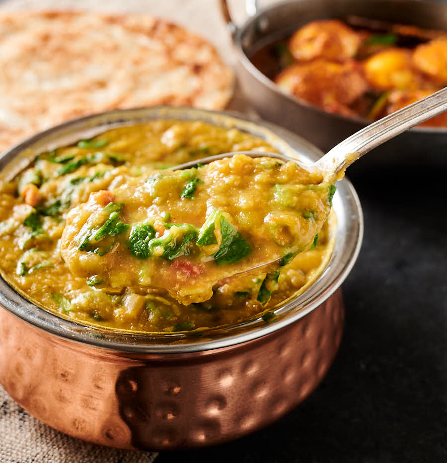 Spoonful of lentil curry with spinach with parathas and egg curry in the background.
