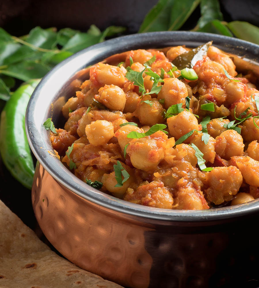 South Indian chana masala in a copper bowl close up.