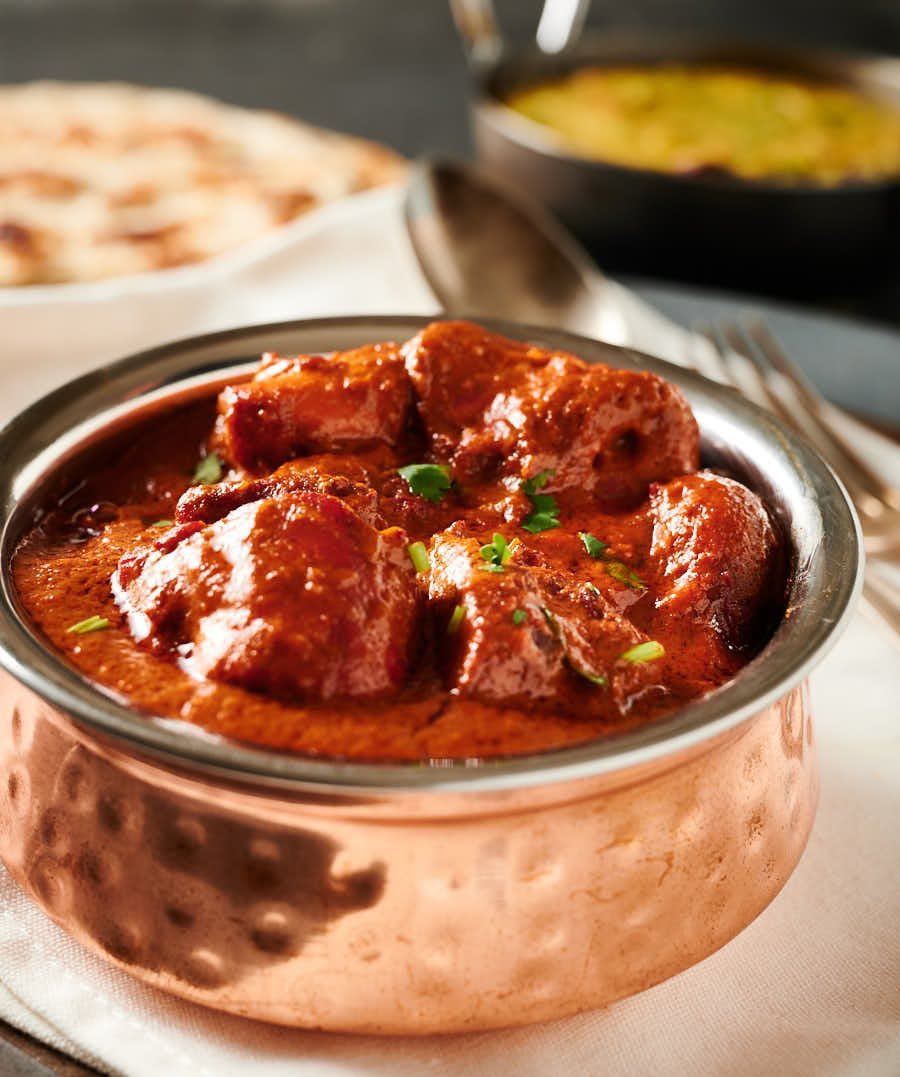 Chicken tikka masala in an Indian copper bowl from the front.