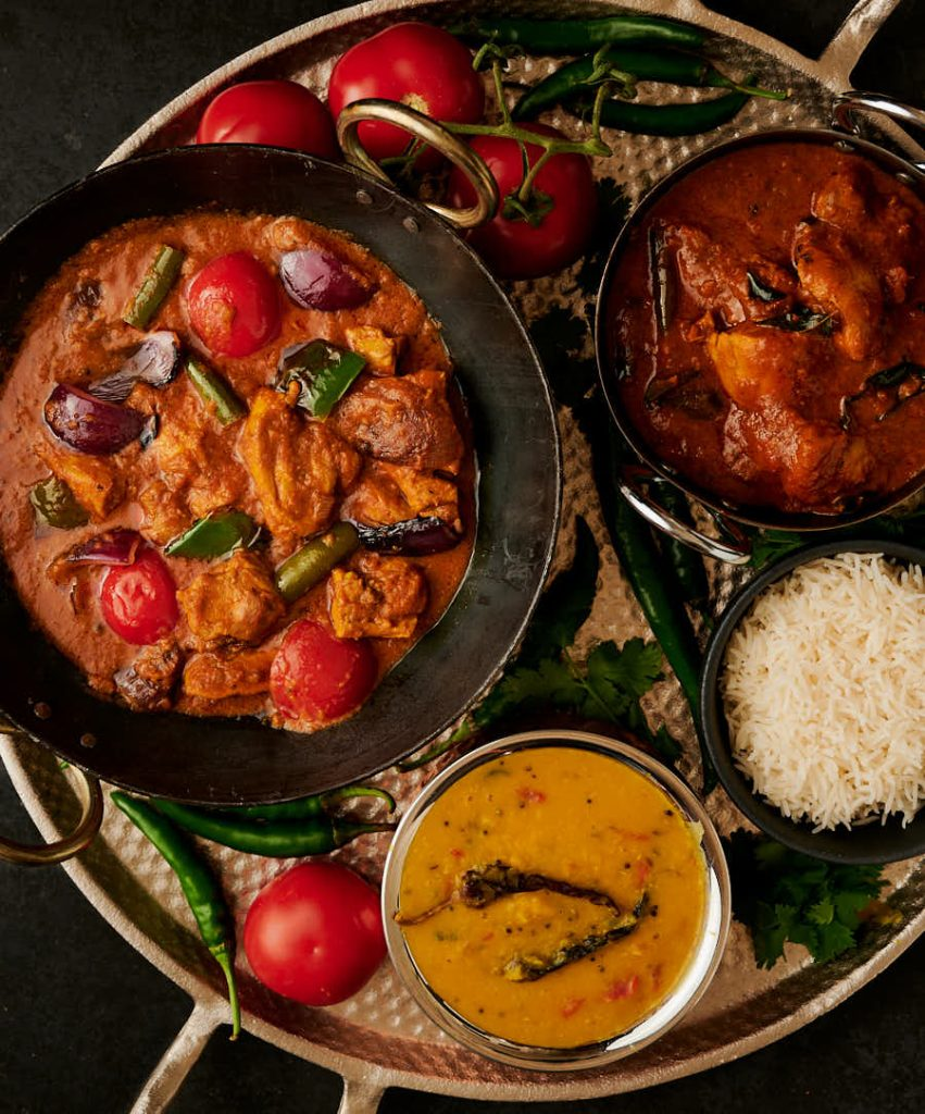 Chicken jalfrezi in a kadai surrounded by curries, dal and and rice.