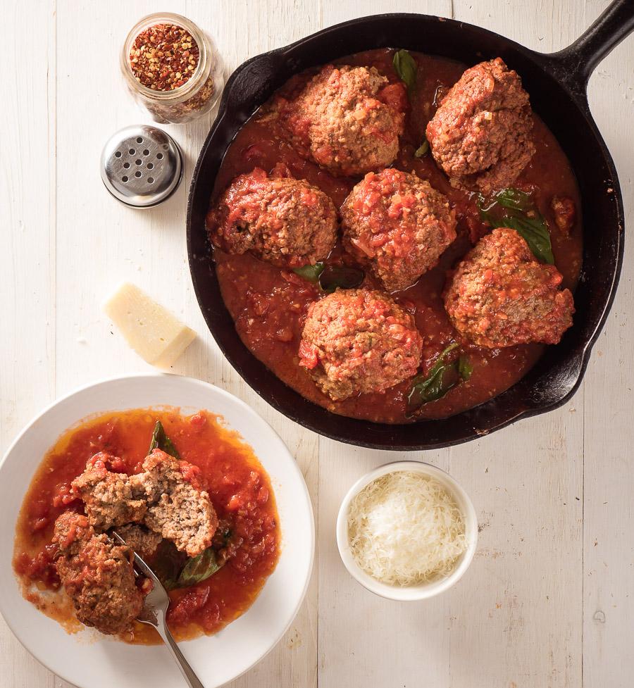 raos meatballs in marinara in a black cast iron frying pan