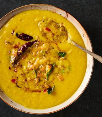 Mixing bowl of tarka dal with tarka mixed in partially from above.