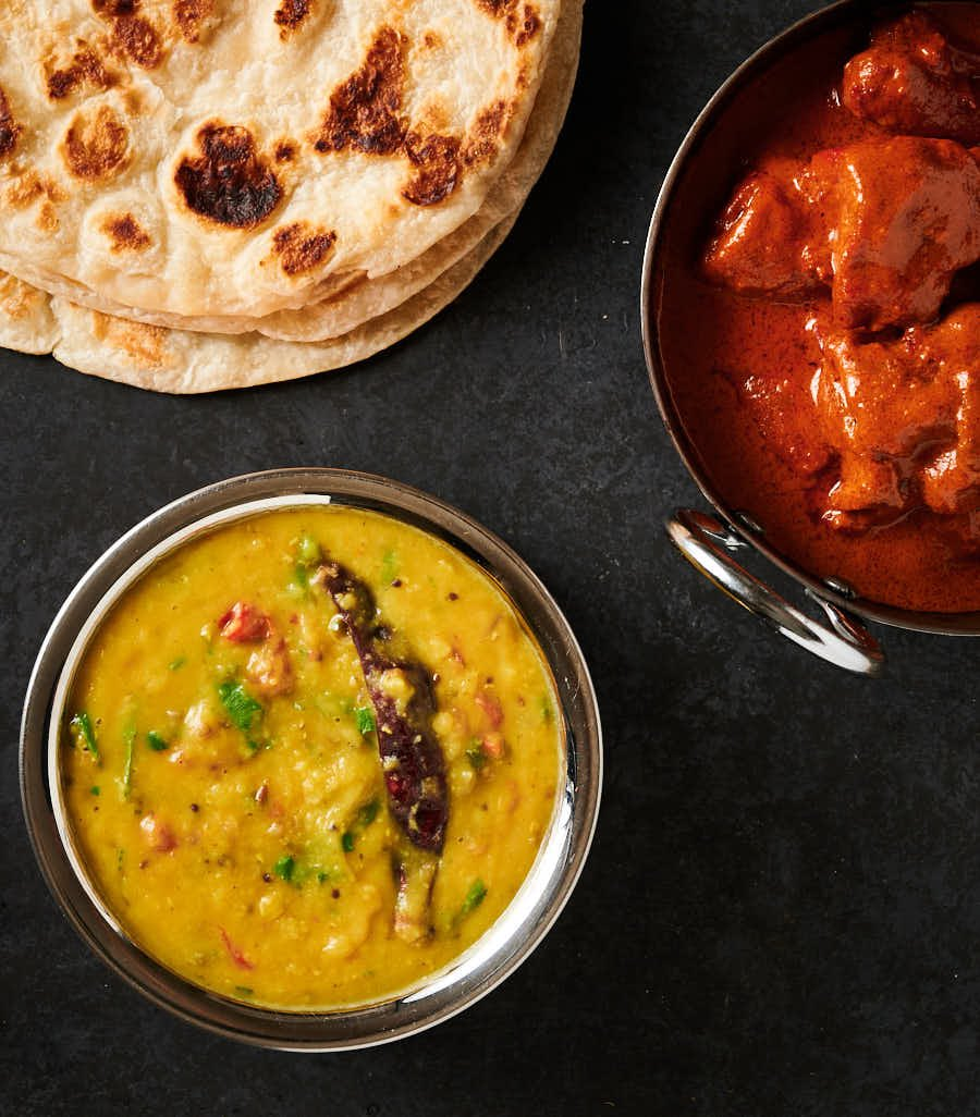 Tarka dal table scene with parathas and chicken tikka masala from above.