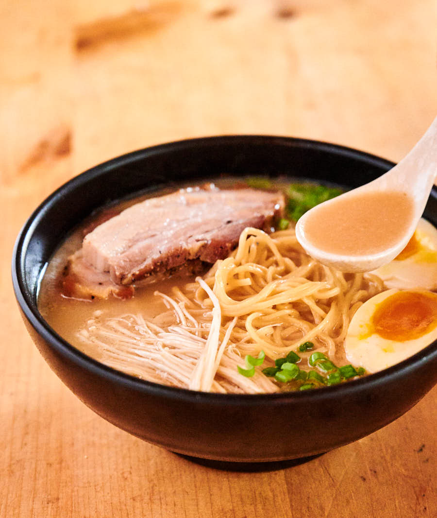 Spoonful of tonkotsu ramen broth above the bowl.