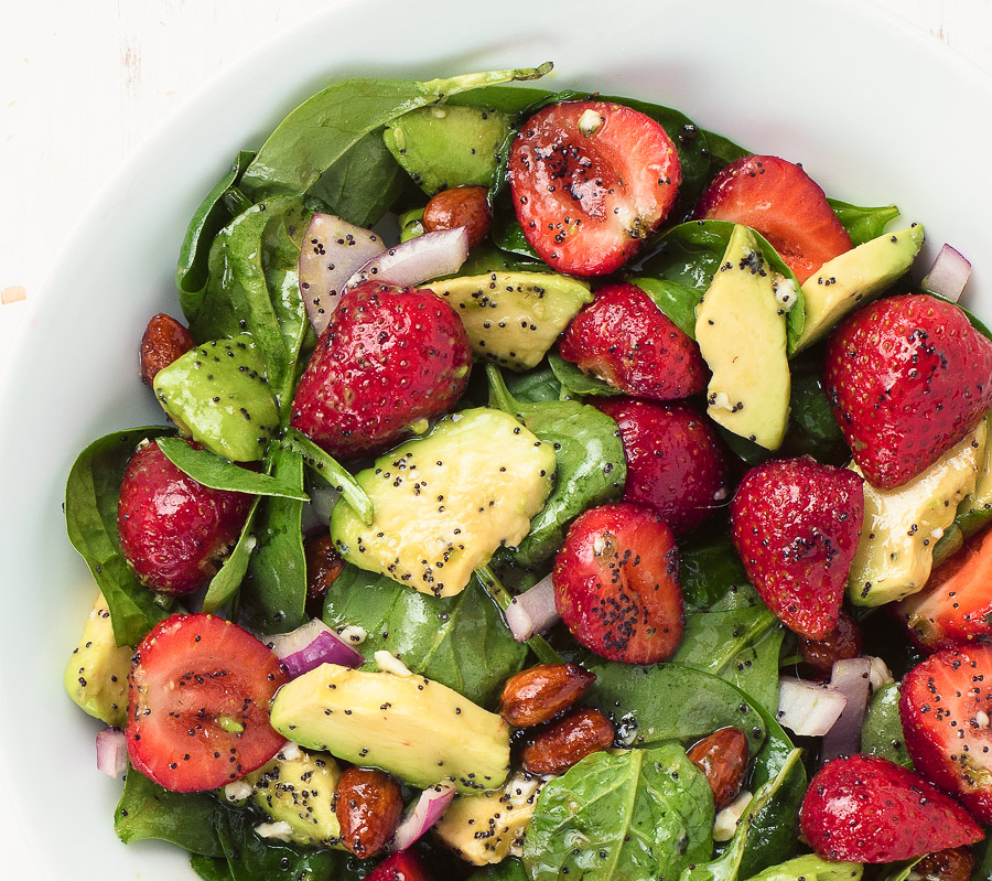Spinach and strawberry salad in a white bowl up close.