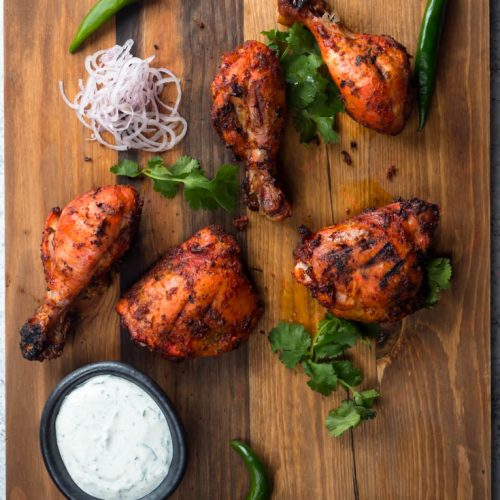 Tandoori chicken on a board from above.