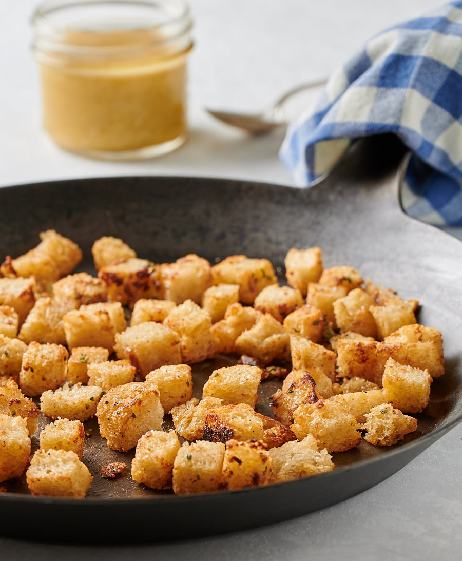 Golden, buttery croutons in a dark skillet from the front.