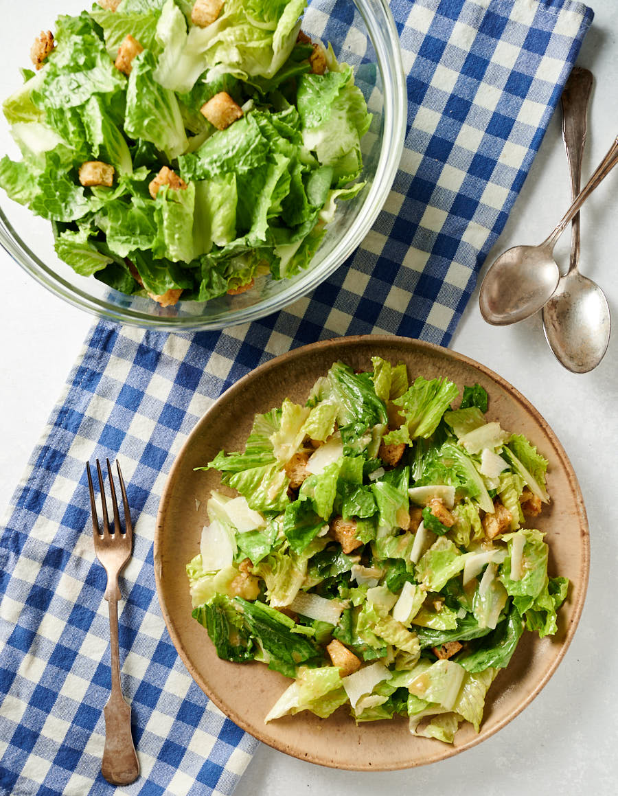 Caesar salad on plate and in salad bowl from above.