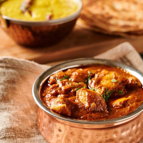 Restaurant style pathia curry in a copper bowl from the front.