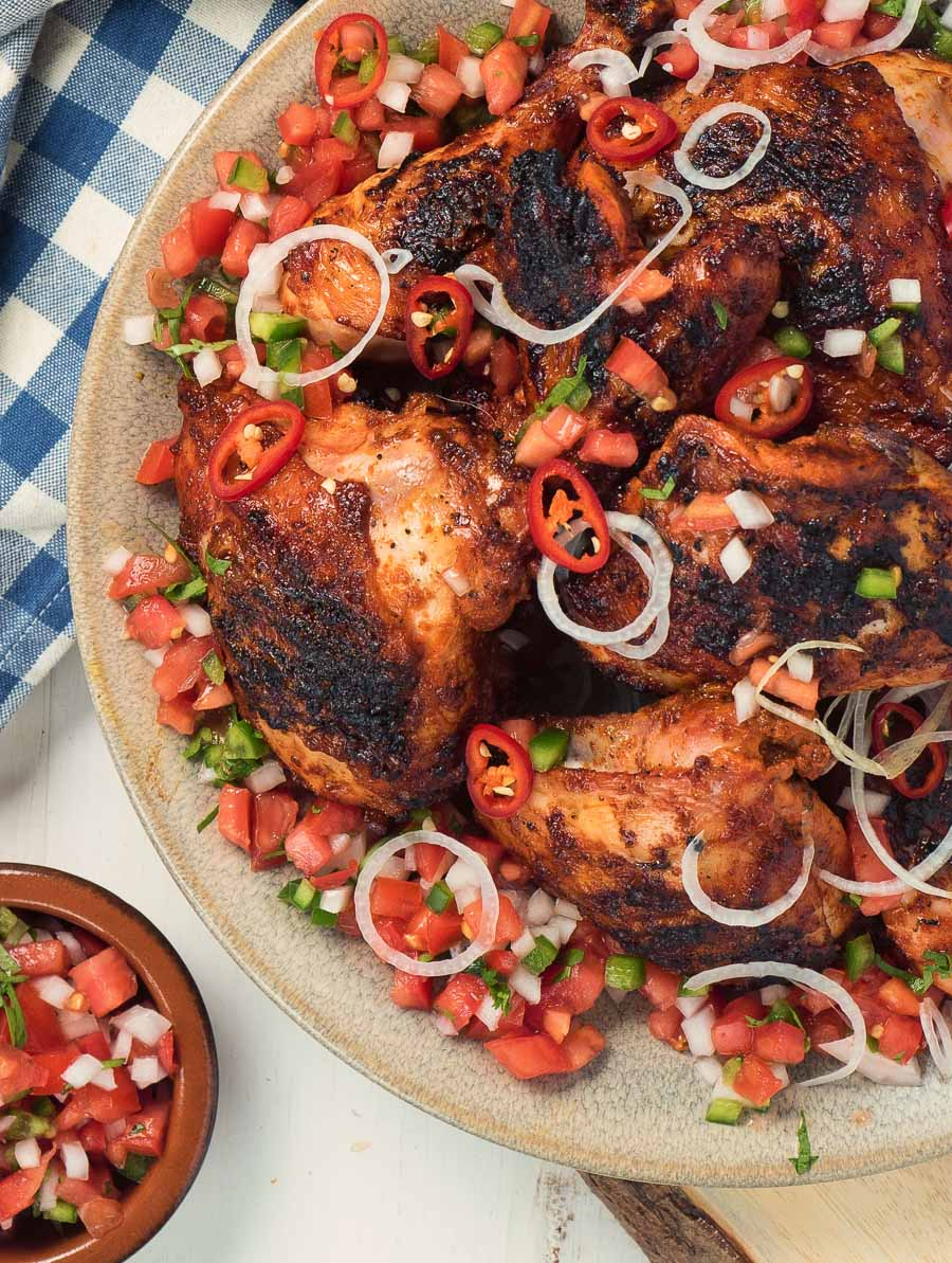 Yucatan grilled chicken on a plate with pico garnish.