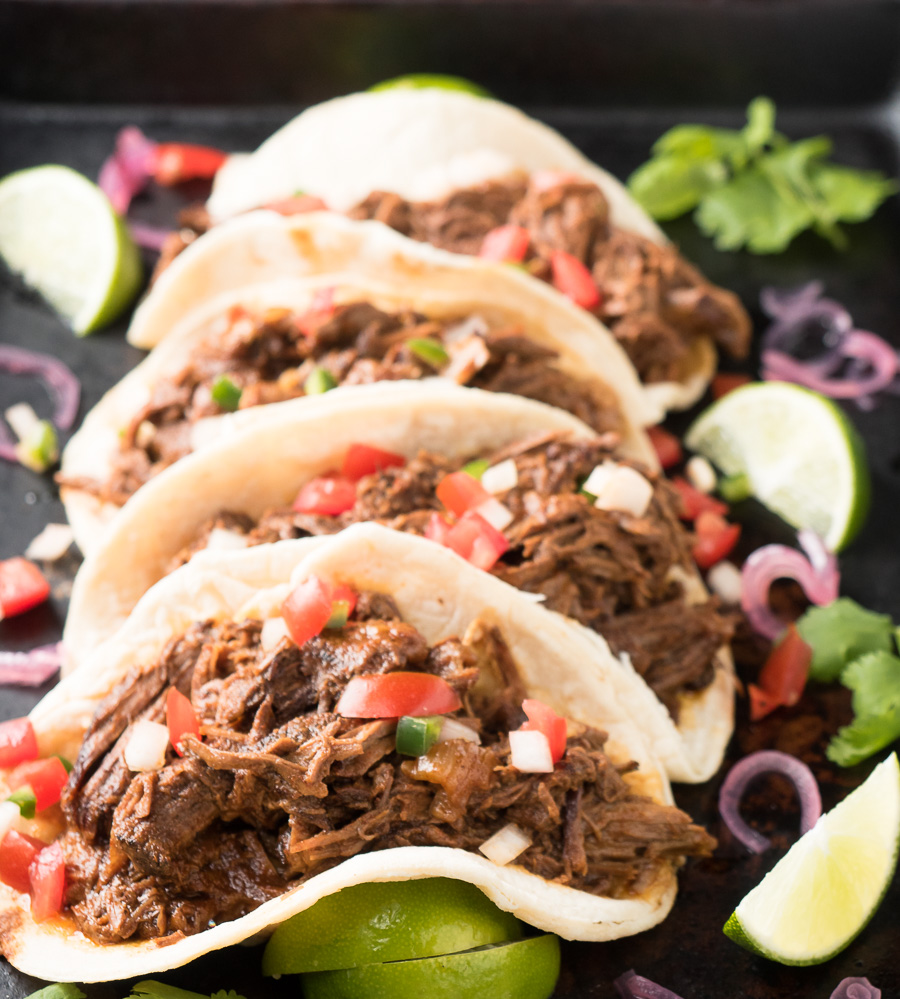 Row of beef barbacoa tacos from the front.