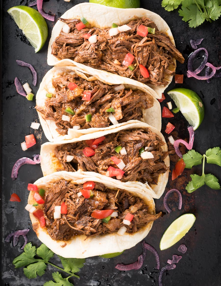 Row of beef barbacoa tacos with pico di gallo from above.