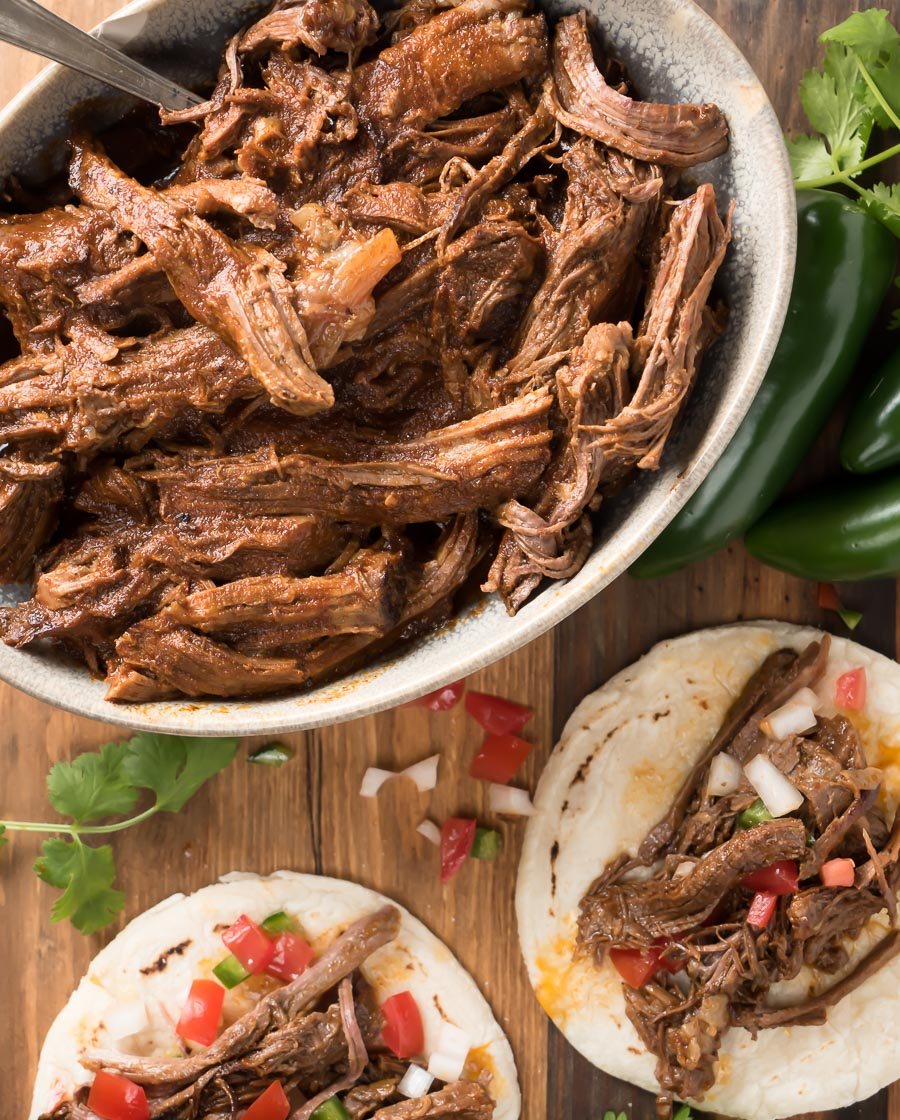 Bowl of beef barbacoa with dressed tacos.