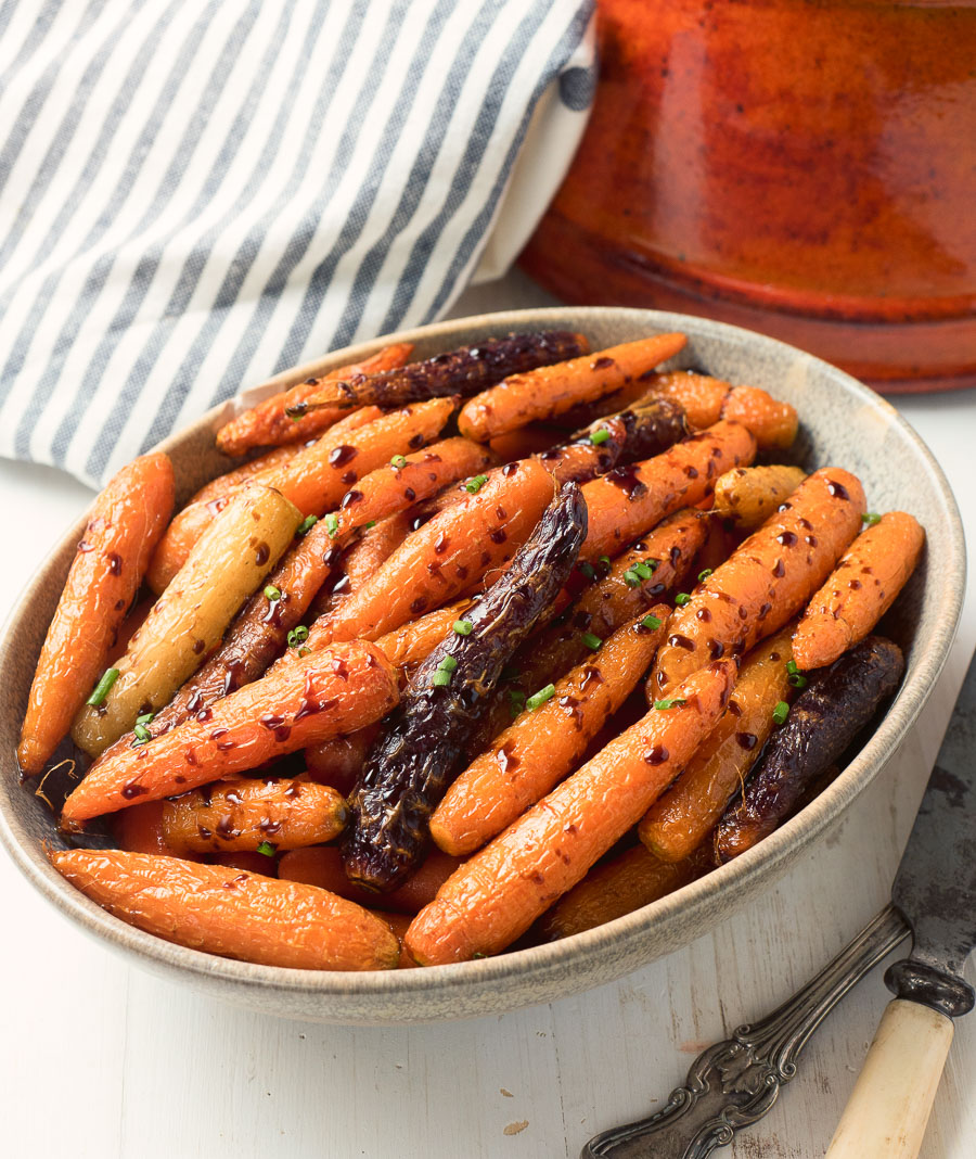 Balsamic roasted carrots in a clay bowl from above.