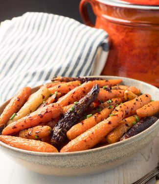 Balsamic roasted carrots in a clay bowl.