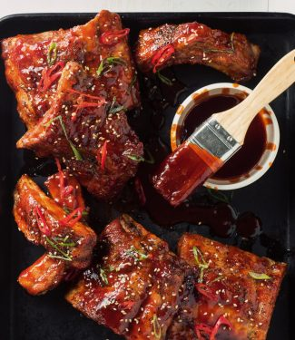 Racks of sticky Korean pork ribs with dipping sauce.