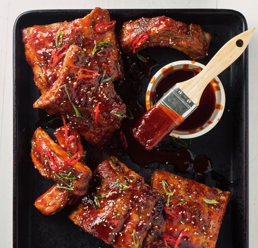 Racks of sticky Korean pork ribs with dipping sauce.