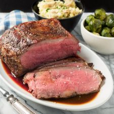 Perfectly medium rare roast beef with demi-glace sauce with fleur de sea garnish.