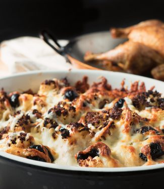 Roasted cauliflower gratin with browned melted cheese and olives front view.