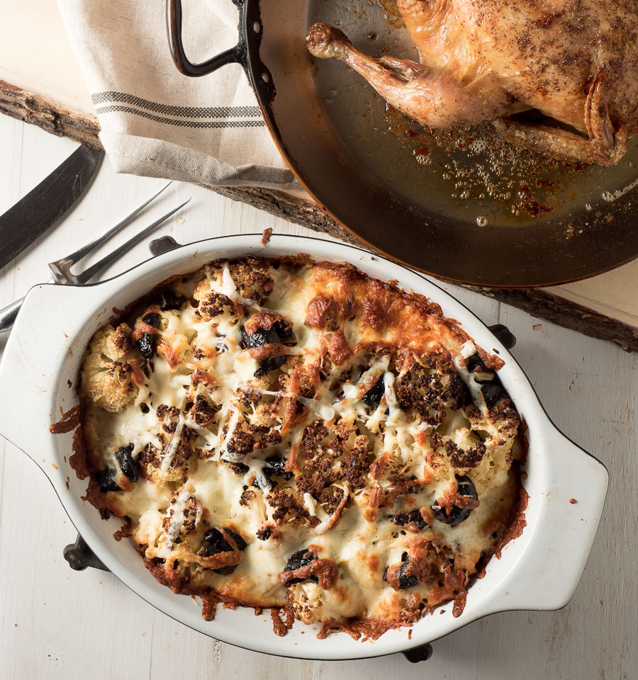 Roasted cauliflower gratin with golden brown melted cheese and olives from above.