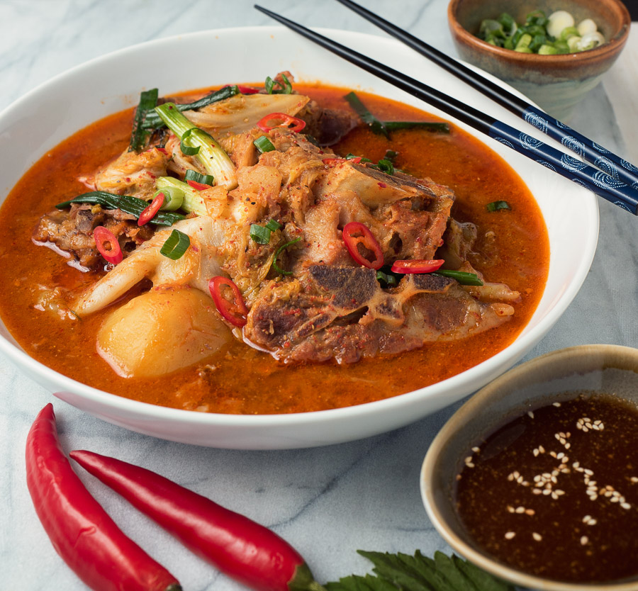 Korean pork bone soup with red chilies in rich pork broth .