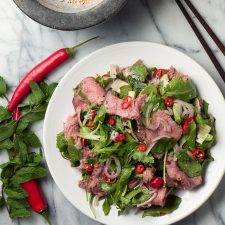 Overhead view of spicy Thai beef salad garnished with red chili slices.