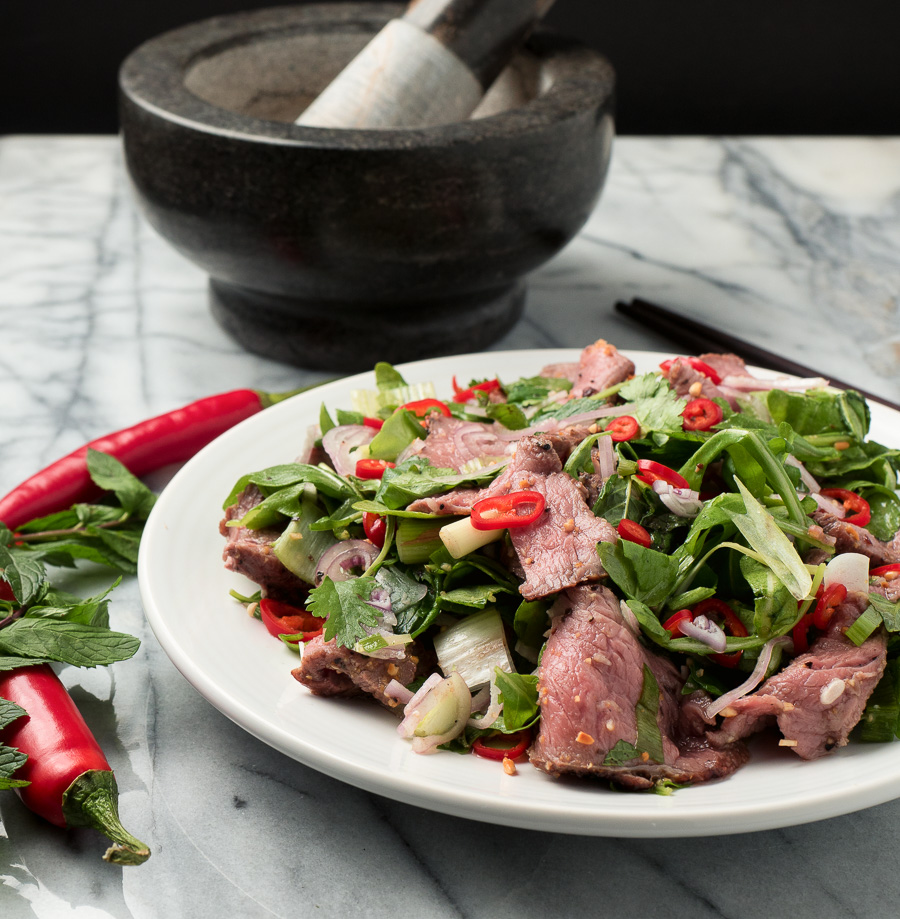 spicy thai beef salad on a white plate garnished with red chili front