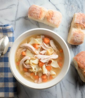 chicken noodle soup from scratch in white bowl with bread