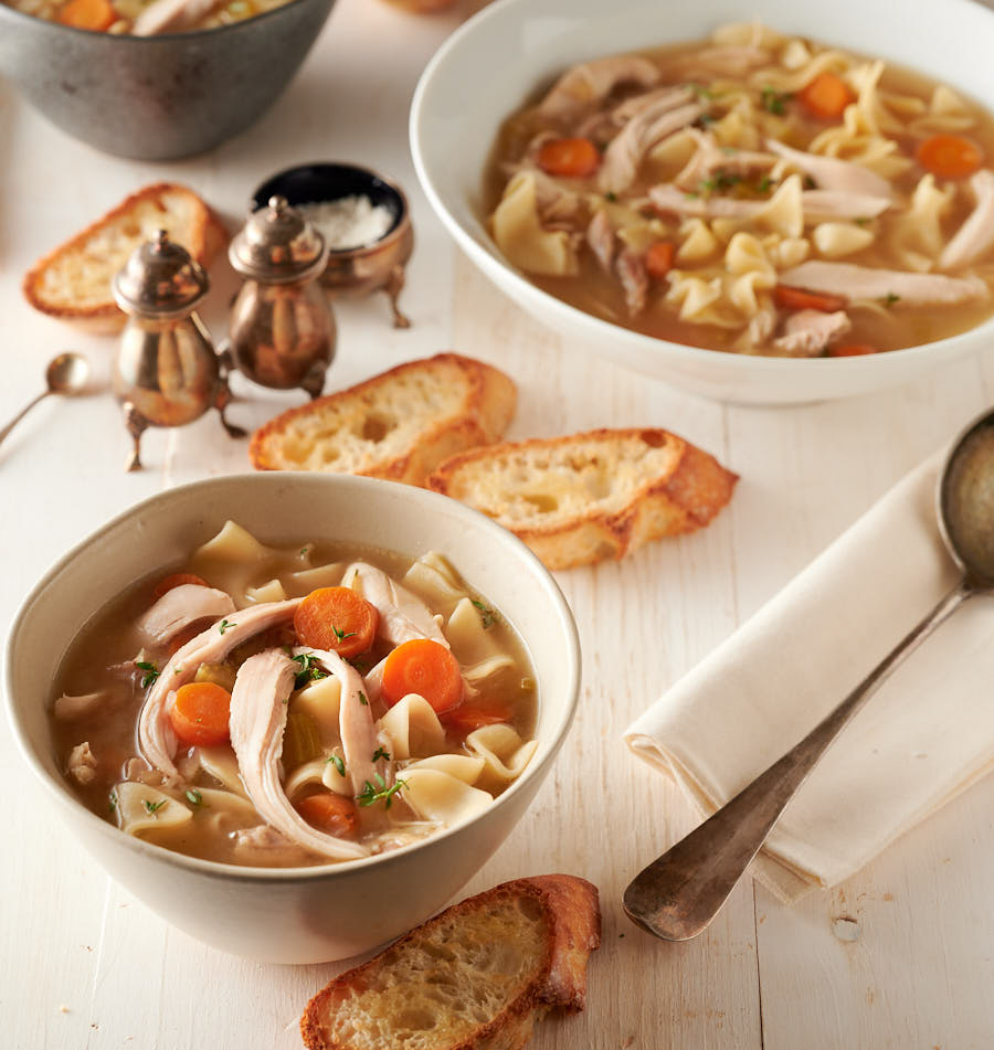 Bowl of homemade chicken noodle soup with bread.