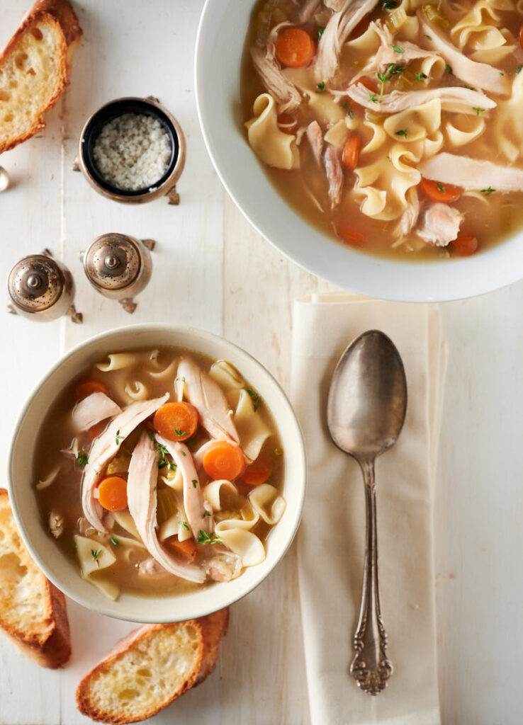 Bowl of chicken noodle soup with spoon from above.